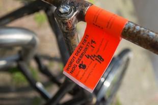 Op het stuur van een fiets zit een oranje label voor verwijdering