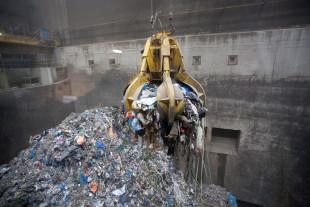 Afbeelding bij Afval Energie Bedrijf. Een machine grijpt afval uit een grote afvalberg