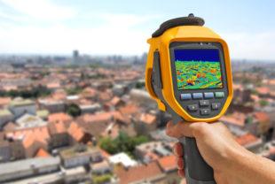 Afbeelding bij verduurzaming warmtevoorziening. en digitale meter meet hoeveel warmte er uit huizen in een wijk ontsnapt