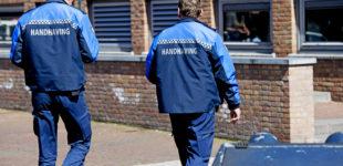 Afbeelding bij onderzoek Handhaving en overlast. Twee handhavers lopen bij een gebouw