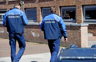 Twee handhavers lopen bij een gebouw