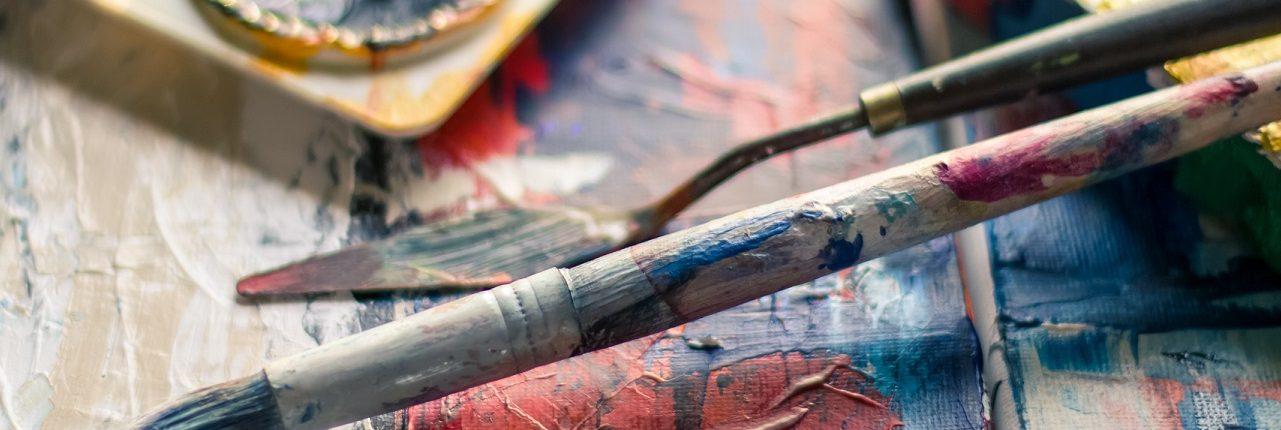 Twee gebruikte penselen liggen op een schilderdoek