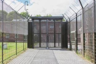 Een gevangenispoort omgeven door hekken en prikkeldraad