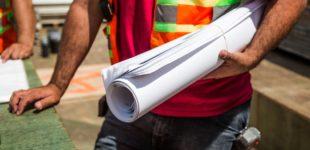 Afbeelding bij onderzoek Transformatiefonds. Een bouwvakker houdt een opgerolde bouwtekening vast