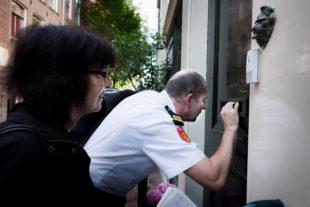 Een handhaver kijkt door een brievenbusgleuf of mensen in het pand aan de Schipperstraat aanwezig zijn.