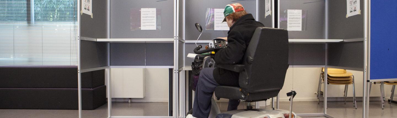 Afbeelding bij Toegankelijkheid van stemlocaties. Een man in een rolstoel brengt zijn stem uit in een stemhokje