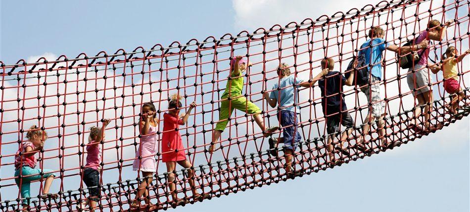 Kinderen klauteren in een rode touwbrug