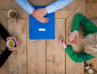 Een kind zit aan tafel met twee volwassenen