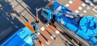 Twee wagens legen het riool op een kruispunt in Amsterdam; een voorbeeld van de uitvoering van de gemeentelijke rioolwatertaken